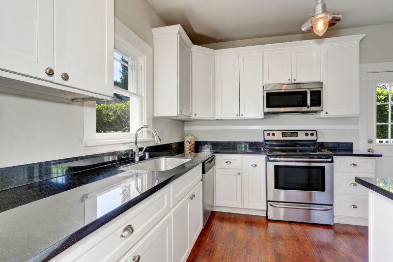 White kitchen room interior with granite counter top and hardwood floor. Northwest, USA